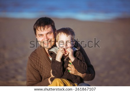 A young dark-haired man is smiling widely and embracing his five-year-old  son, who's laughing, putting his fingers into his mouth. Clothes: casual. - stock photo