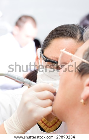 A young dentist treating an old woman's teeth whit the turbine, a blurred male doctor in the background - part of a series. - stock photo