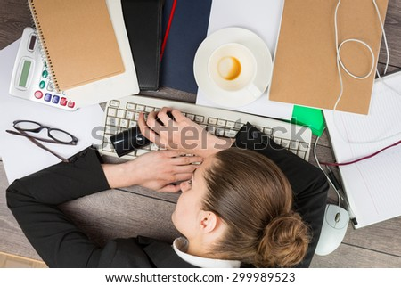 A young desperate businesswoman sleeping on desk in office. Top view. A lot of work time pressure at work. Working hard - stock photo