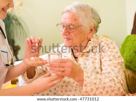 A young doctor giving medications - drugs and vitamins - and a glass of fresh water to an elderly woman. - stock photo