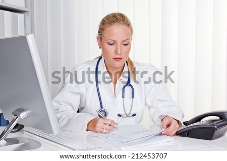 a young doctor with stethoscope in her doctor's office. - stock photo