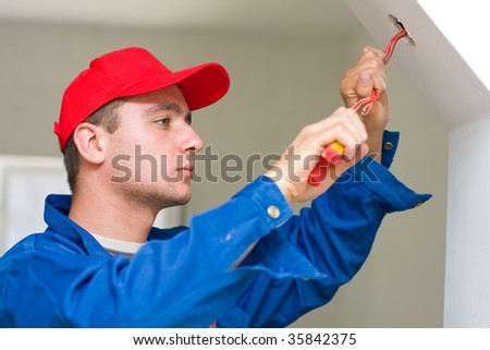A young electrician installing lights in a new house - part of a series. - stock photo