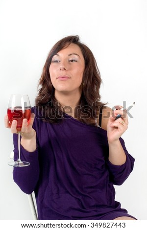 a young elegant woman drinking wine, smoking a cigarette - stock photo