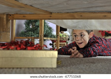 A young elementary boy in his pajamas reaching toward a wrapped gift under his parents' bed. - stock photo