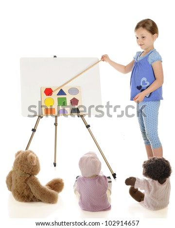A young elementary girl teaching her toys about shapes.  On a white background. - stock photo