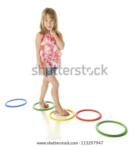 A young elementary girl walking a path of colorful rings.  On a white background. - stock photo