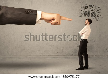 A young employee disagreeing and arguing with boss, feeling ashamed concept. A large hand pointing at businessman saying no - stock photo