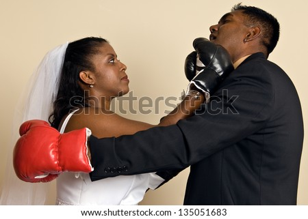 A young ethnic couple wedding attire wearing boxing gloves. She connects with a right hook, showing her husband who's boss. - stock photo