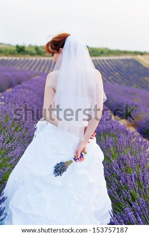 A young European woman in a wedding dress stands back, a hand bouquet of lavender, lavender field on background - stock photo