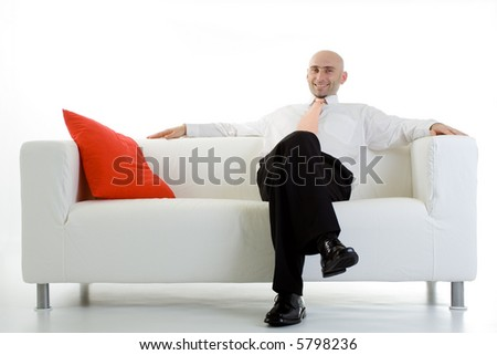 A young executive leans back, relaxing on the couch. - stock photo