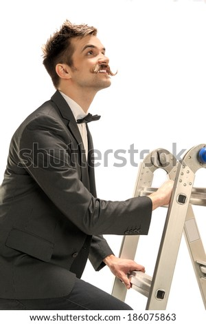A young executive looks up into the light as he climbs a ladder toward heaven or success - stock photo