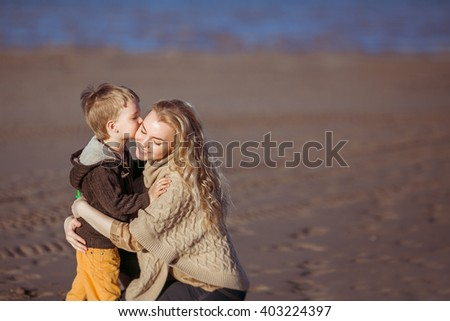 A young fair-haired woman is sitting on her haunces on the sand, embracing her small son who's kissing her. Clothes: casual. - stock photo