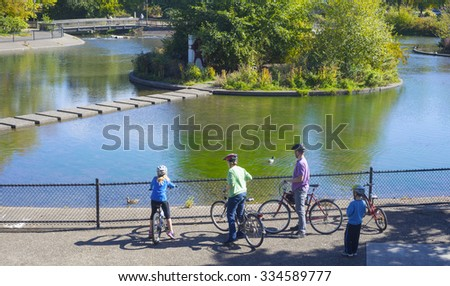A young family observe ducks at Alton Baker Park in Eugene Oregon. - stock photo