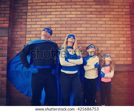 A young family of super heroes are standing outside with blue capes and masks looking up for a protection, strength or creativity concept - stock photo