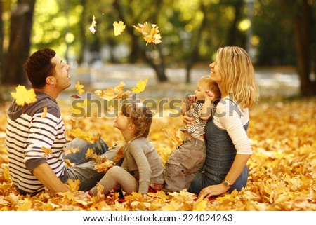 a young family playing in autumn park outdoors - stock photo