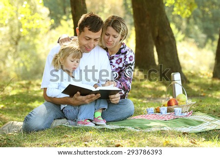 a young family read the Bible in nature - stock photo