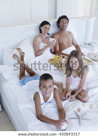 A young family with young children to bed in the bedroom - stock photo