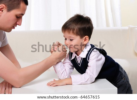 A young father and his young son struggling in the arms - stock photo