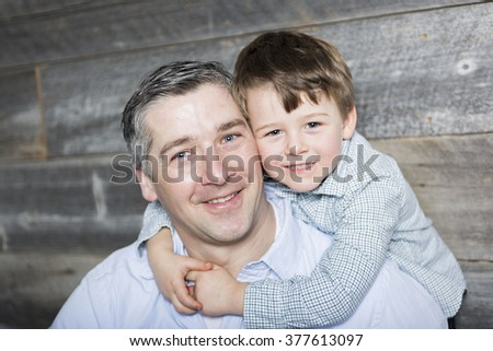 A Young father with son in studio wood background - stock photo