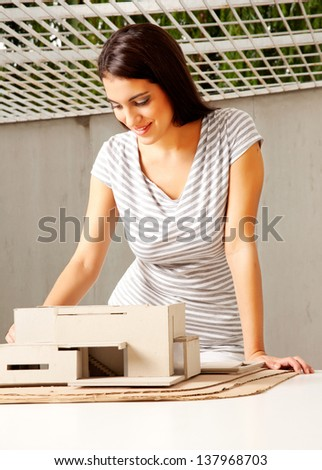 A young female architect looking over a rough model of a house - stock photo