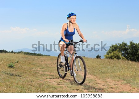 A young female biking a mountain bike outdoors - stock photo