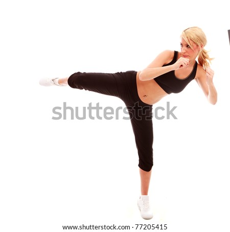 A young female dressed in black gym clothes performing a karate kick on isloated white background - stock photo