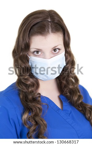 A young female health care worker with mask on covering her nose and mouth to prevent catching or spreading germs and disease. - stock photo