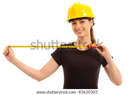 a young female holding a tape measure wearing a safety hat - stock photo