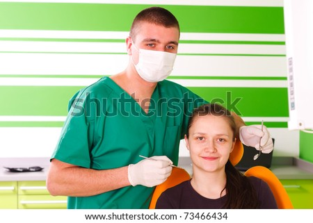 A young female patient at the dentist smiling,  being happy for the dental treatment. - stock photo