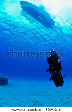 A young female scuba diver looks up as a speeding boat zooms over head on a dive in Mexico. - stock photo