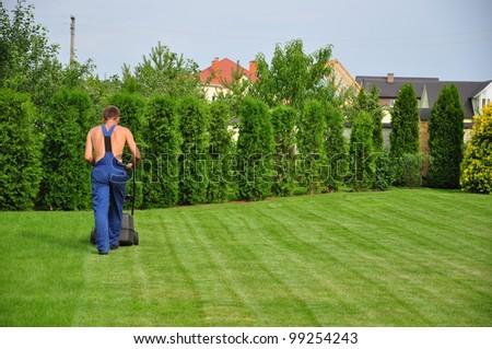 a young gardener cutting grass on garden - stock photo