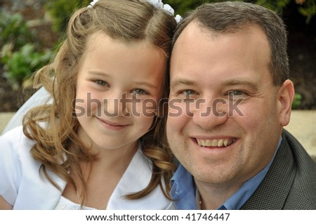 a young girl and her father on first communion day - stock photo