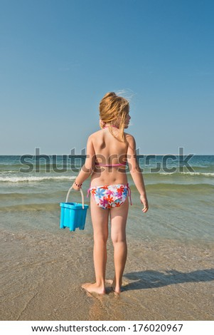 A young girl at the beach holding a pail. - stock photo