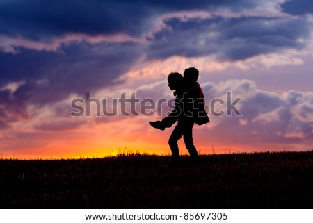 A young girl carries her brother on her back at sunset. - stock photo