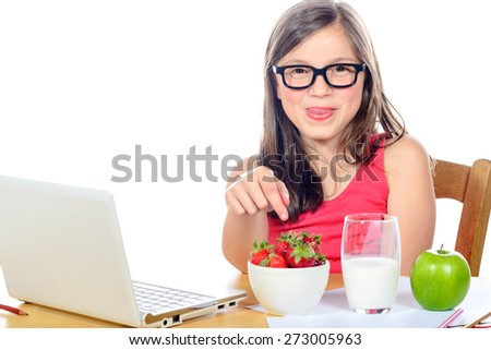 a young girl chooses strawberries on white background - stock photo