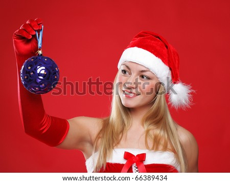 A young girl dressed as Santa Claus on a red background holds a New Year's toy - stock photo