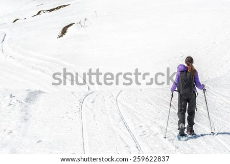 A young girl during a trip snowshoeing, in a snowy landscape. - stock photo