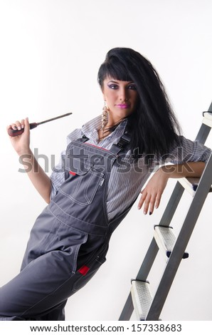 A young girl electrician in a overall with screwdriver - stock photo
