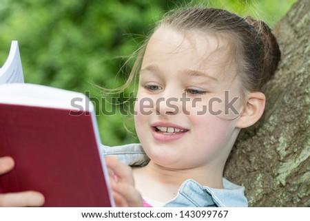 A young girl enjoying reading a book - stock photo