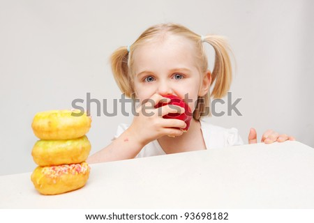 A young girl enjoys eating a healthy apple which she has chosen rather than the unhealthy donuts. - stock photo