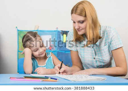 A young girl explains the five-year girl how to write letters - stock photo