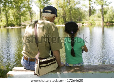 A young girl fishing with her grandpa on a warm summer day. - stock photo