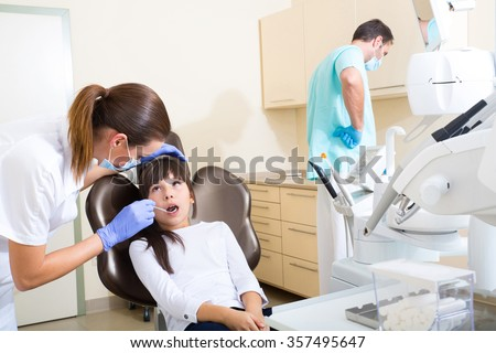 A young girl getting her dental checkup at the dentist. - stock photo