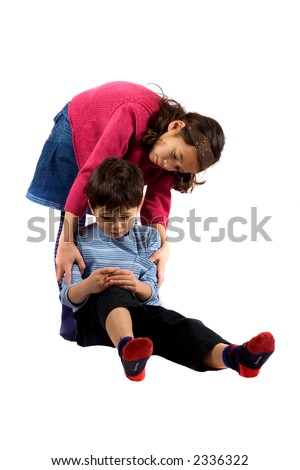 A young girl helping her brother up after he trips over and hurt his knee. - stock photo