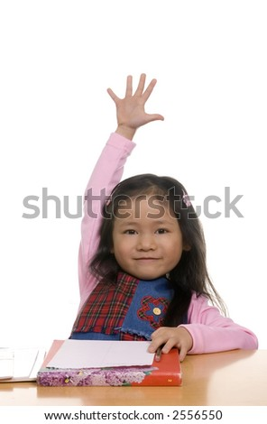 A young girl hold her hand high in the air... pick me I know - stock photo