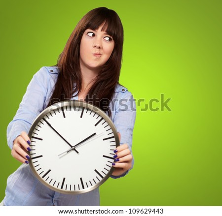 A Young Girl Holding A Clock And Making Face On Green Background - stock photo