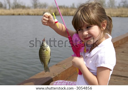 A young girl holding a fish she just caught - stock photo