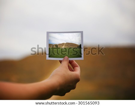 a young girl holding an instant photo like a polaroid in front of a landscape that is the same but a close up instead of a wide angle toned with a retro vintage instagram filter app or action effect - stock photo
