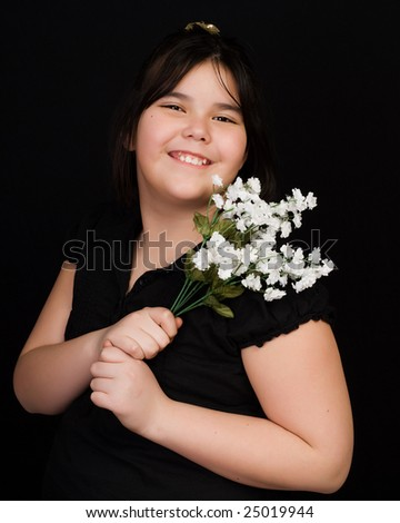 A young girl holding some silk flowers, shot against a black background - stock photo