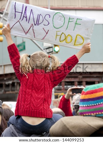 A young girl holds a sign that reads Hands Off My Food above the crowd during a march against genetically modified organisms, also known as GMO's. - stock photo